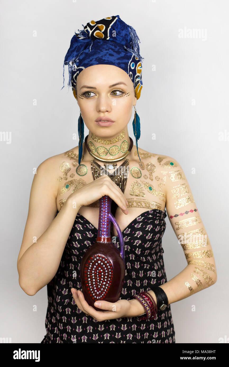 92c7dc89831d Una bella ragazza in stile africano vestiti è in possesso di una brocca