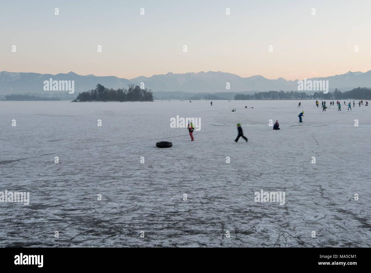 I bambini giocano sulla congelati Staffelsee, hockey su ghiaccio è riprodotto in background Immagini Stock