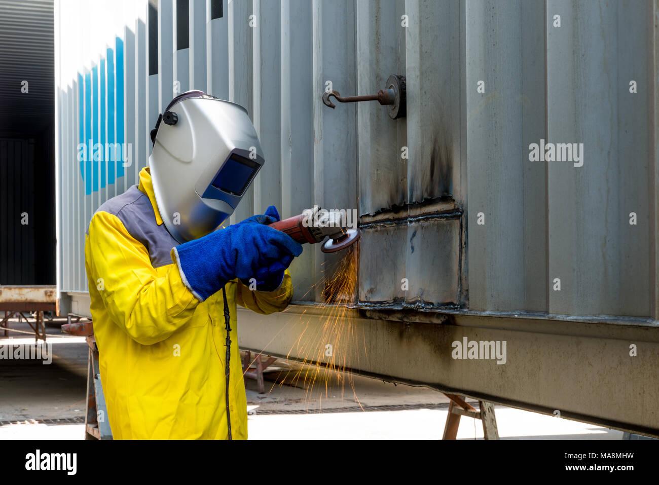 Lavoratore del settore con la molatura di metallo per la riparazione di strutture di contenitore fabbricazione workshop. Lavoratore di macinazione in industria di fabbrica. Immagini Stock