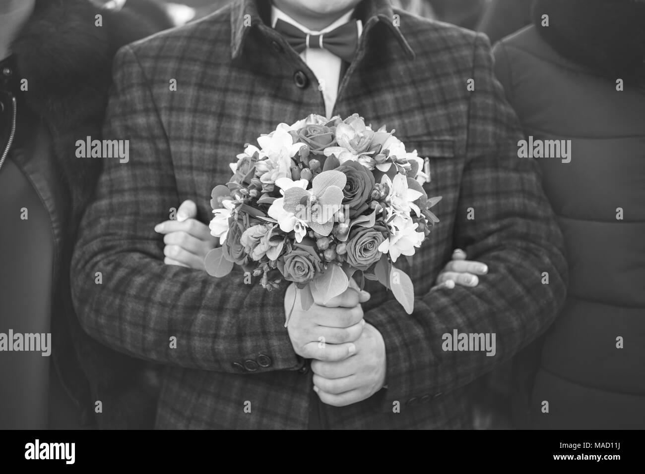 Sposo abiti eleganti con bouquet nelle sue mani sta per sposa, giorno di nozze, in bianco e nero di tonificazione Immagini Stock