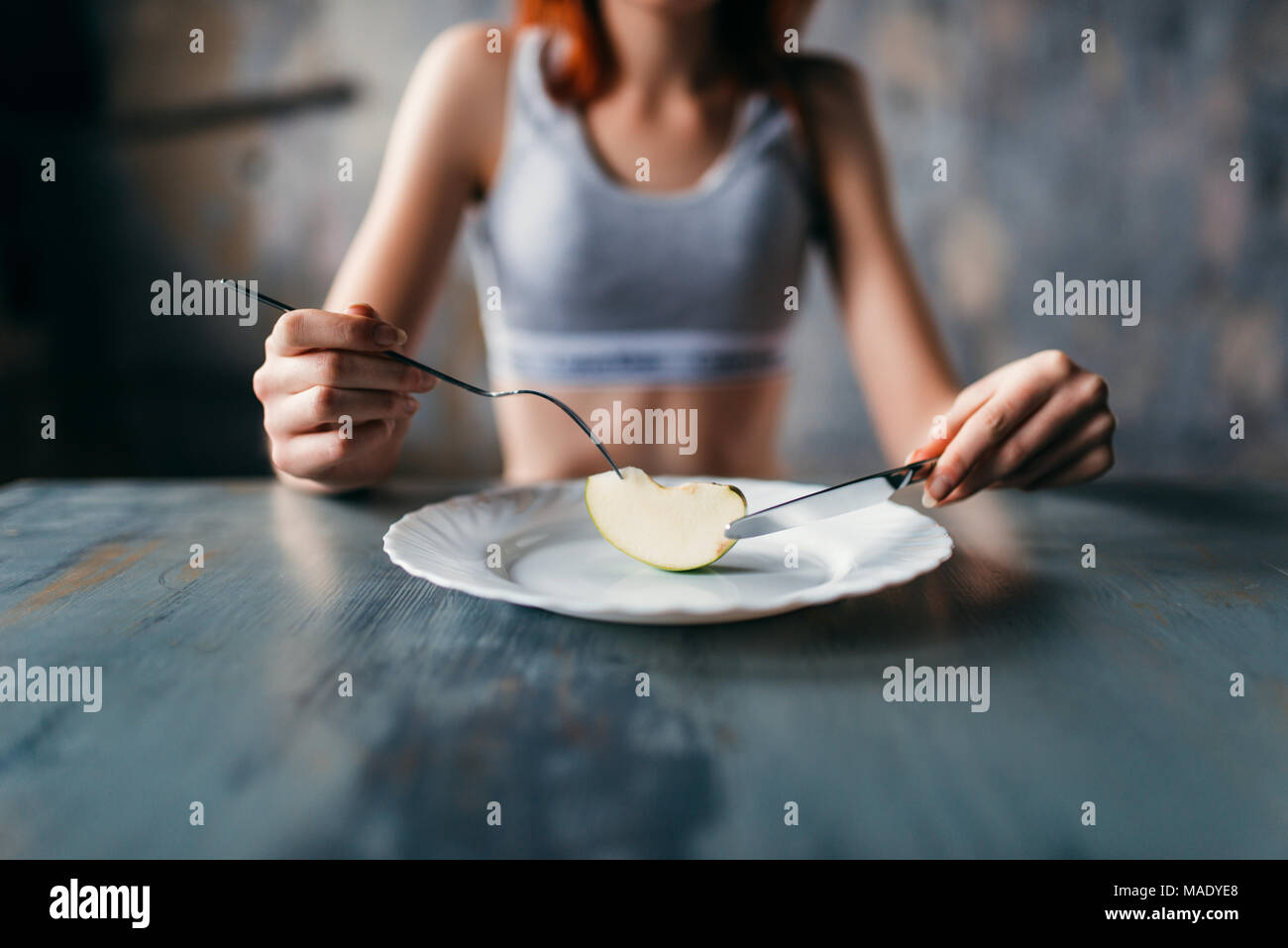 Persona di sesso femminile contro la piastra con una fetta di Apple Immagini Stock