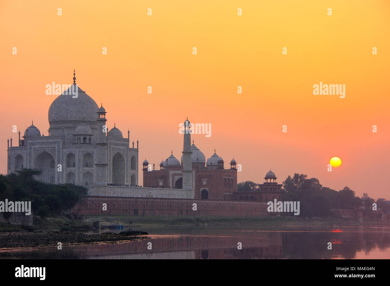 Taj Mahal si riflette nel fiume Yamuna al tramonto in Agra, India. Esso è stato commissionato nel 1632 dall'imperatore Mughal Shah Jahan in casa la tomba di suo fa Immagini Stock