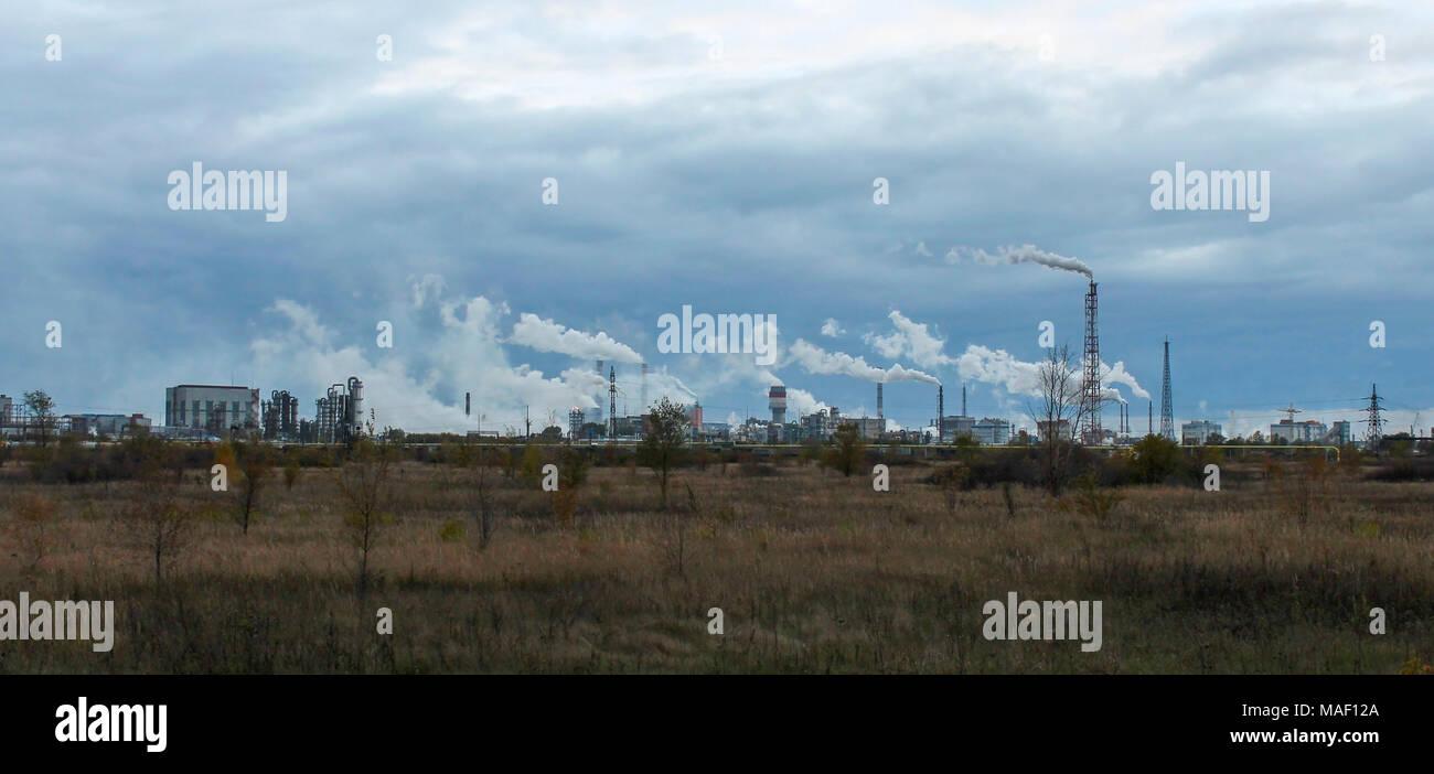 Zona industriale con fabbriche e tubi di fumo e di illuminazione a