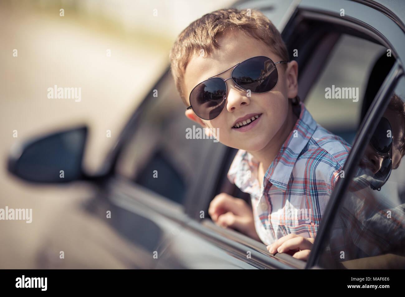 Una felice piccolo ragazzo seduto in macchina al giorno. Concetto di vacanza estiva. Immagini Stock