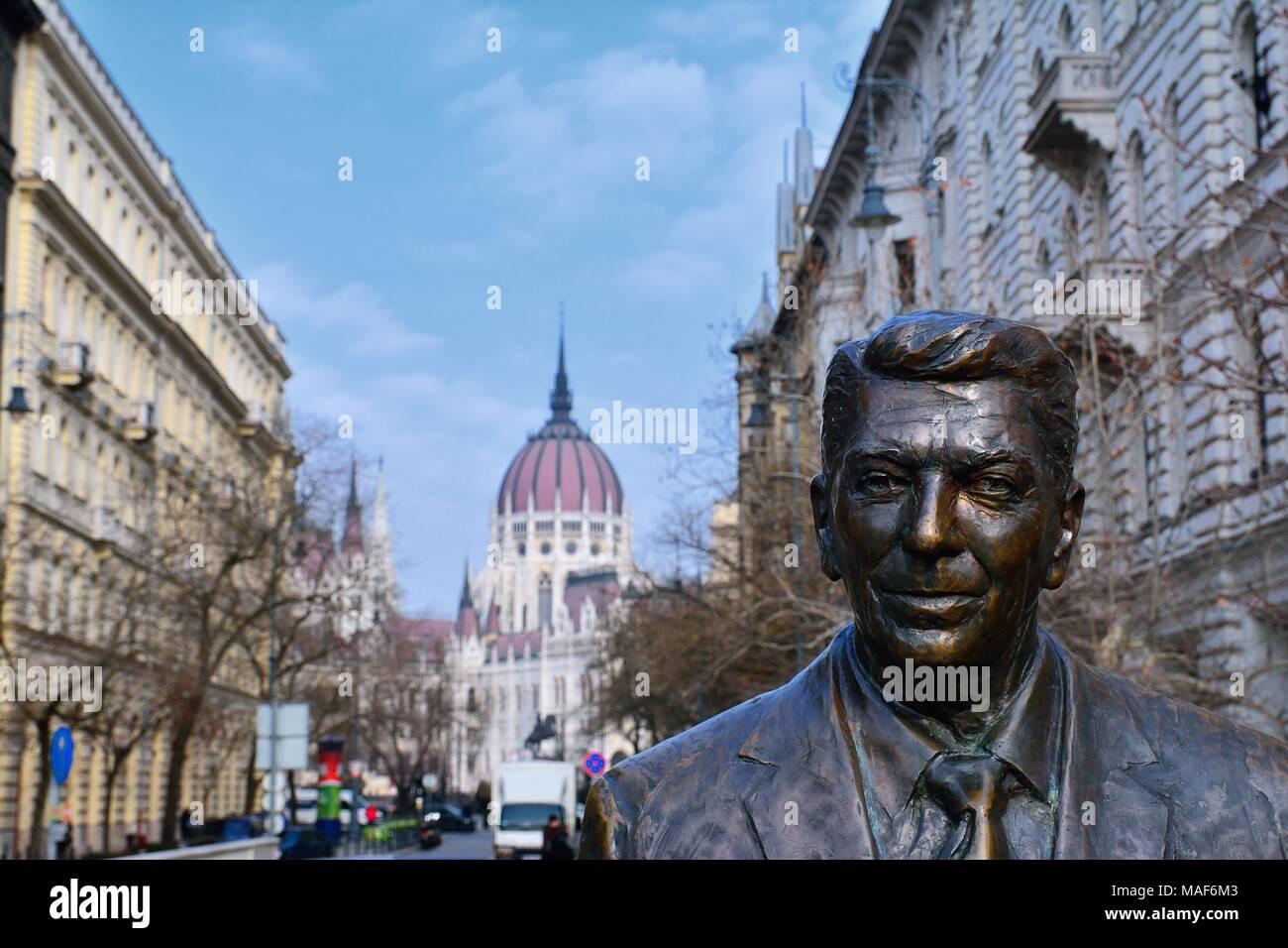 Budapest, Ungheria - 28 Marzo 2018: Statua dell'ex U.S. Il Presidente Ronald Reagan sullo sfondo del parlamento ungherese edificio. Statua di sc Foto Stock