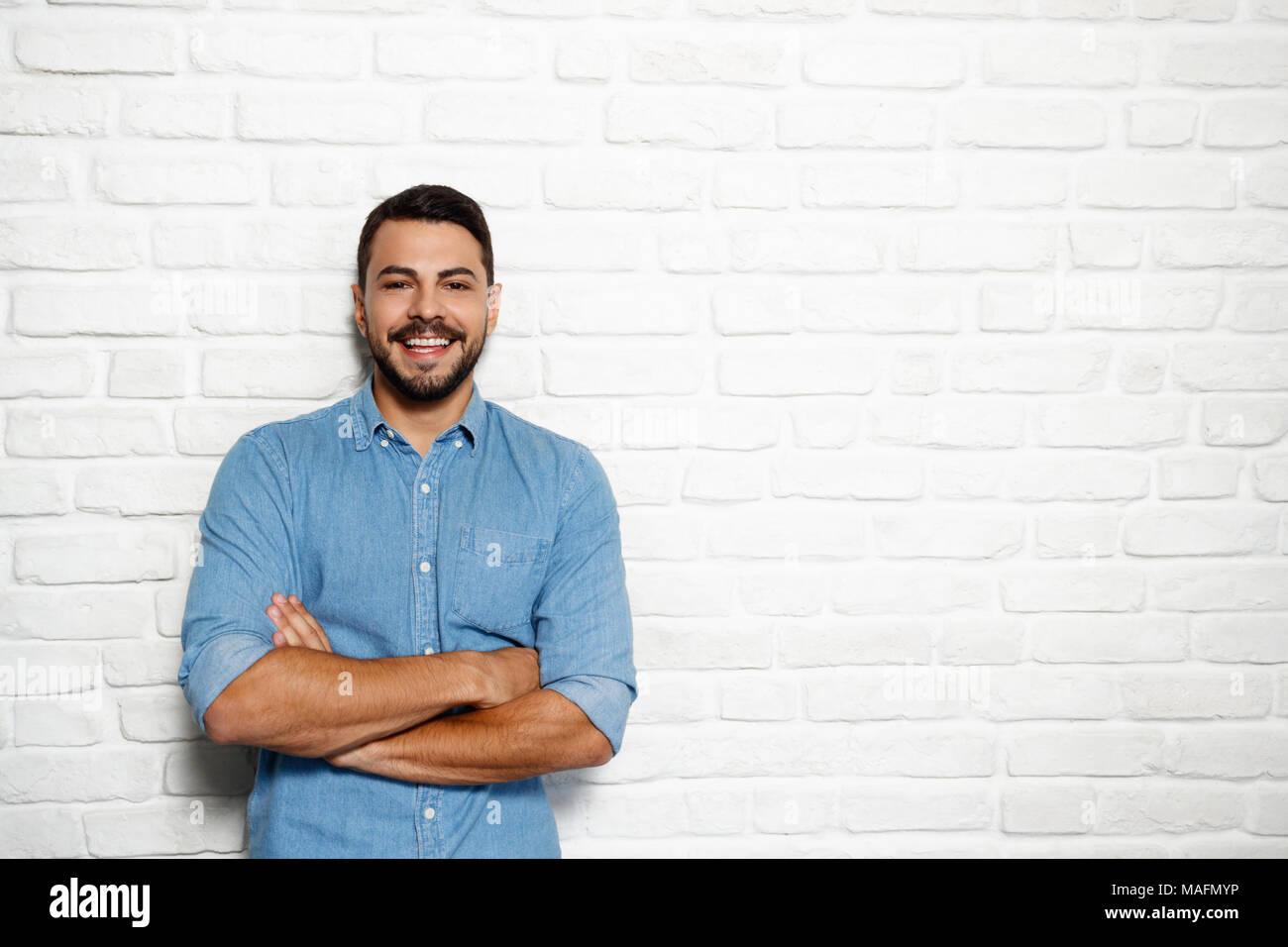 Ritratto di felice italiano uomo sorridente contro il muro bianco come sfondo e guardando la fotocamera. Immagini Stock