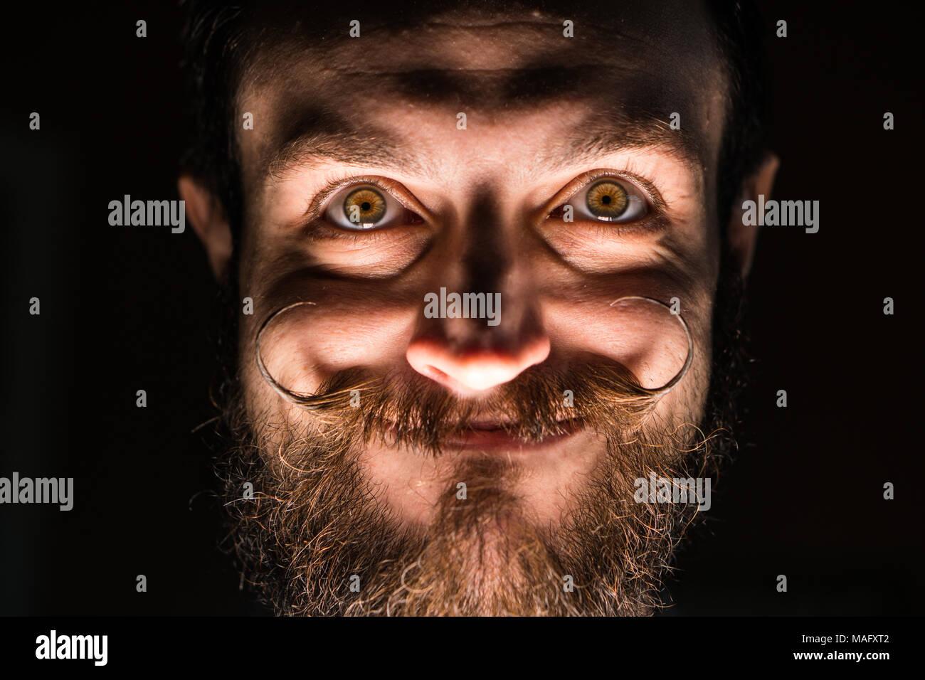 Inventore hipster con la barba e Mustages in camera oscura. Sorridente trickster. Immagini Stock