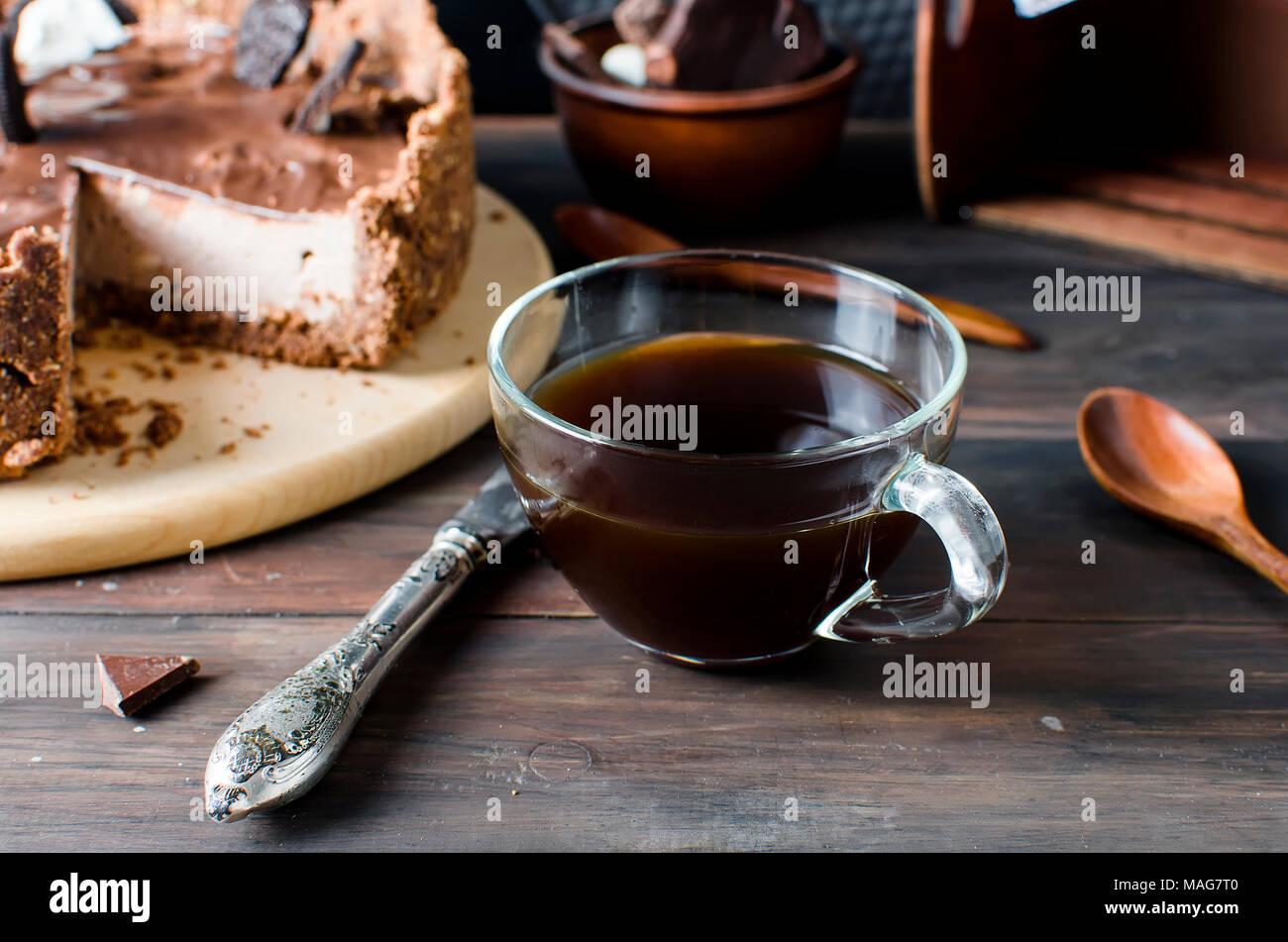 Cheesecake al cioccolato e caffè al buio su un vecchio tavolo di legno, copia di spazio, Immagini Stock