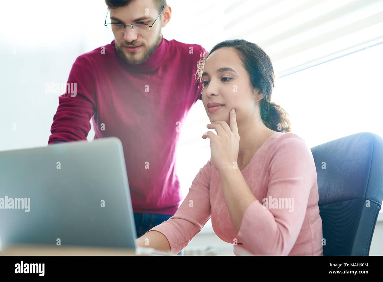 Malinconici dipendenti in sede di progetto di visualizzazione maquette su laptop Immagini Stock