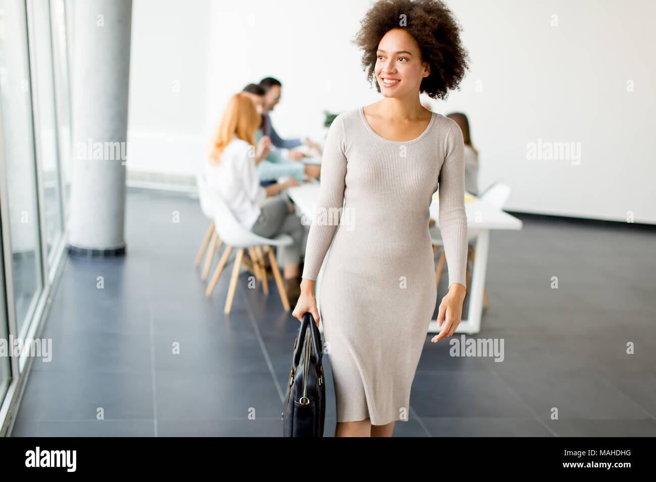 Vista business a persone per discutere di una strategia e di lavorare insieme in ufficio mentre giovane imprenditrice lasciando la carica Immagini Stock