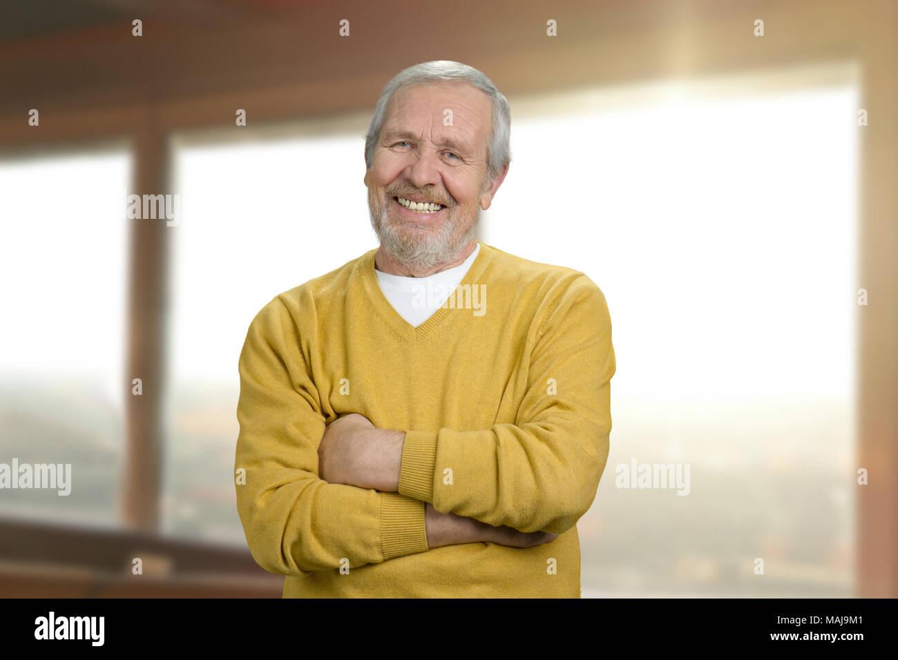 Ritratto del nonno sorridente a casa. Allegro vecchio uomo in felpa gialla  con attraversata bracci fc4e5d6381cb