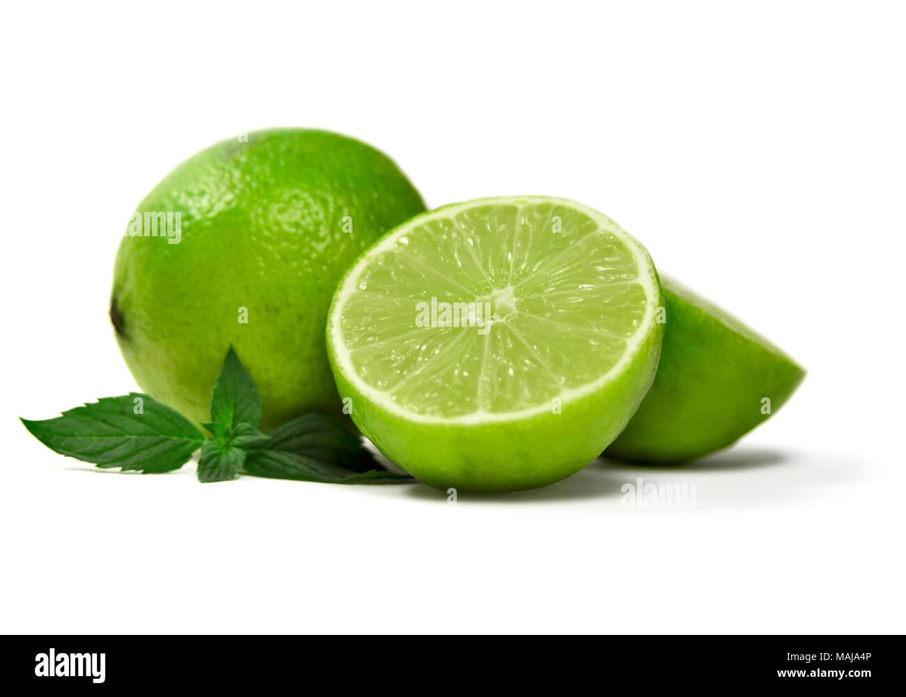 Limette fresche, isolato su sfondo bianco. Sezione trasversale e tutta la calce frutti con foglie di menta, agrumi sfondo. Immagini Stock
