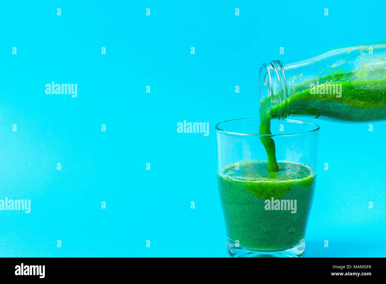 Processo di colata dalla bottiglia di vetro verde frullato fresco da foglie verdi Ortaggi Frutta. Mele banane Kiwi Zucchine spinaci su luce Blu Immagini Stock