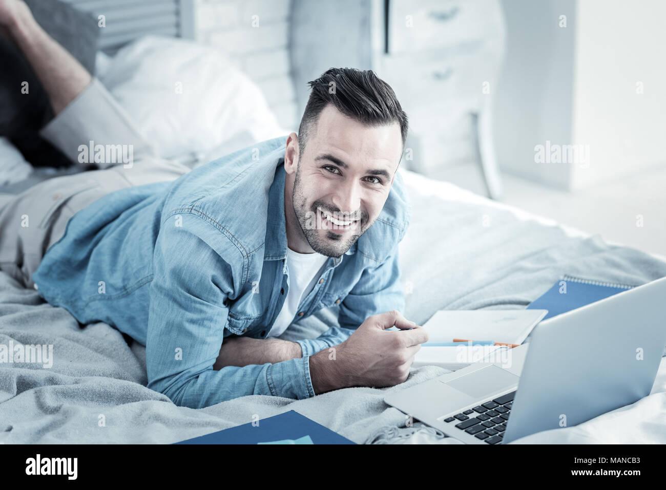 Allegro piacevole uomo studiando da casa Immagini Stock
