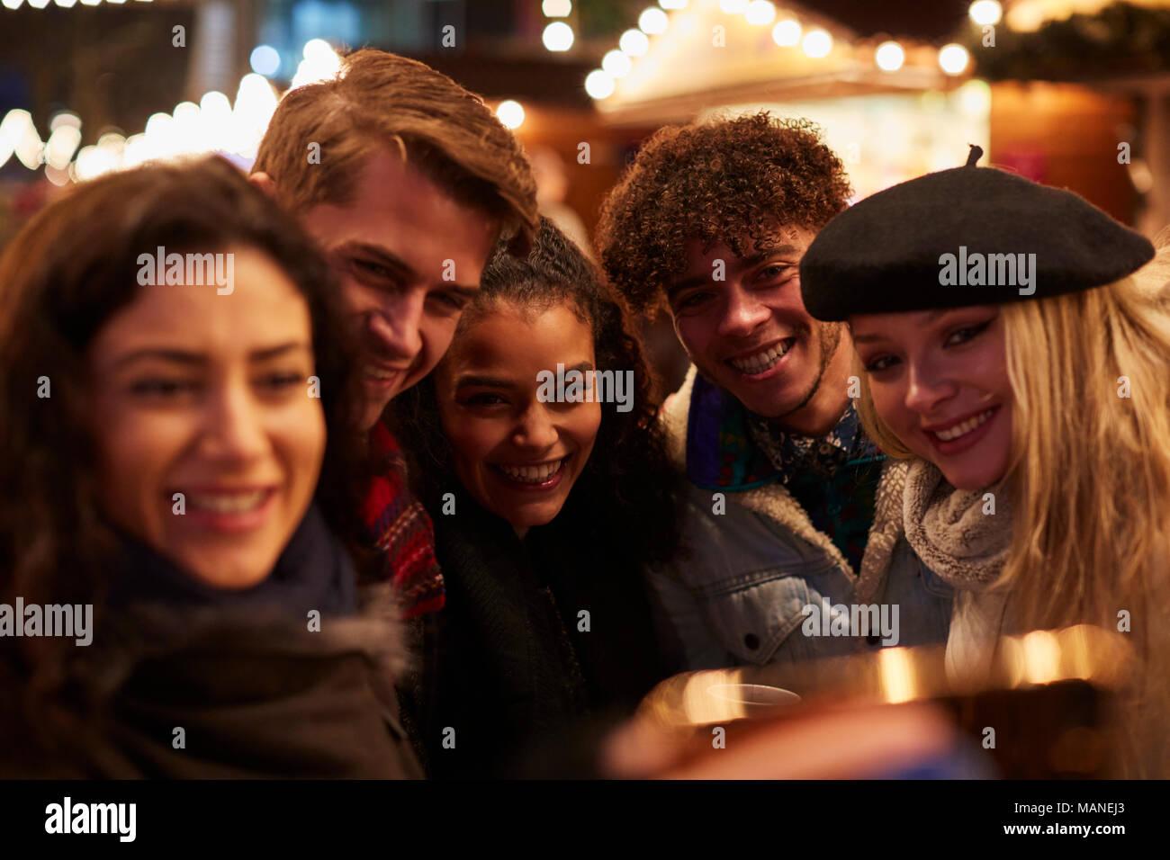 Giovani amici in posa per Selfie Al Mercatino di Natale Immagini Stock