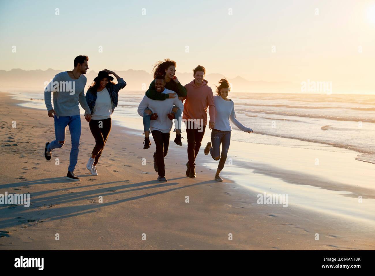 Gruppo di amici divertendosi in esecuzione lungo la spiaggia invernale insieme Immagini Stock