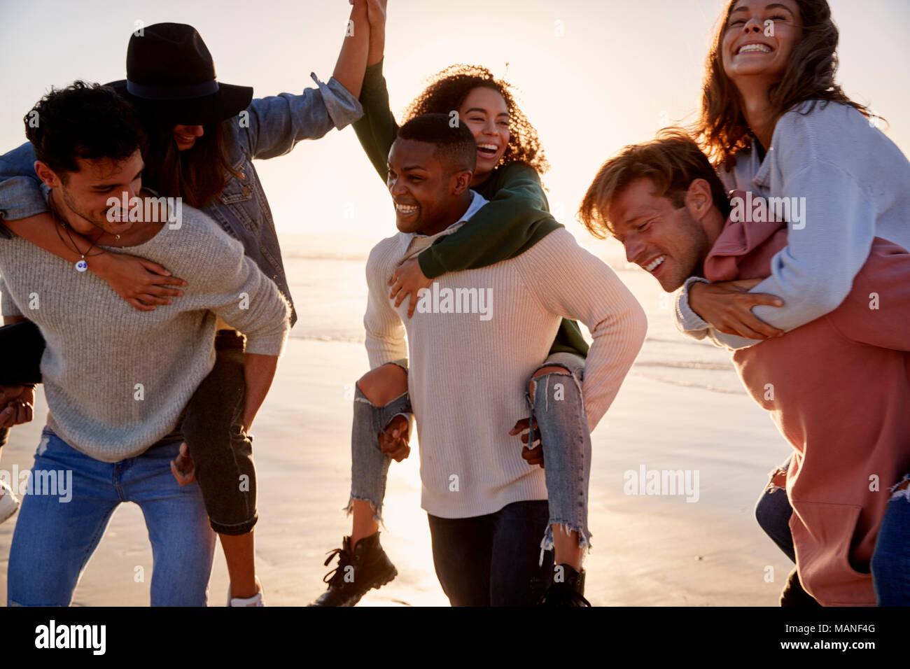 Gruppo di amici avente Piggyback gara sulla Spiaggia Invernale insieme Immagini Stock