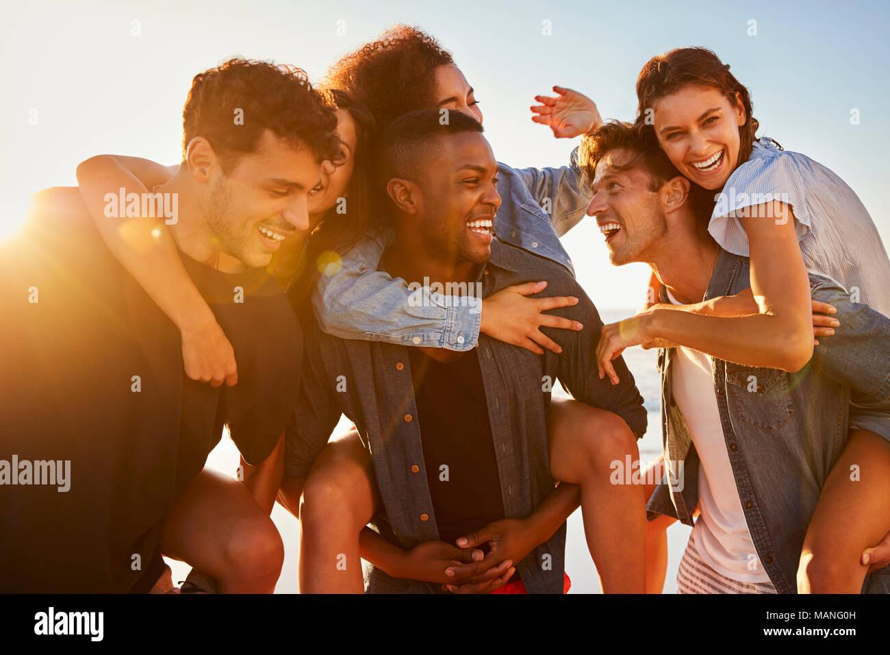 Gruppo di amici in vacanza avente Piggyback gara sulla spiaggia Immagini Stock