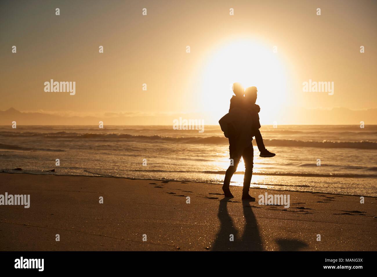 Silhouette di padre dando figlio piggyback sulla Spiaggia Invernale Immagini Stock