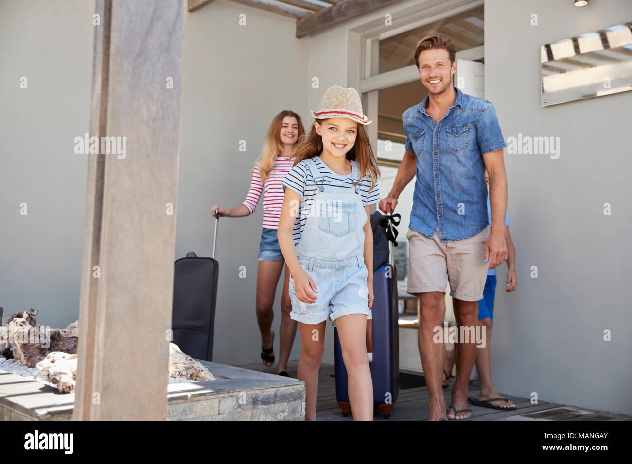 Ritratto di famiglia con i bagagli di lasciare casa per le vacanze Immagini Stock