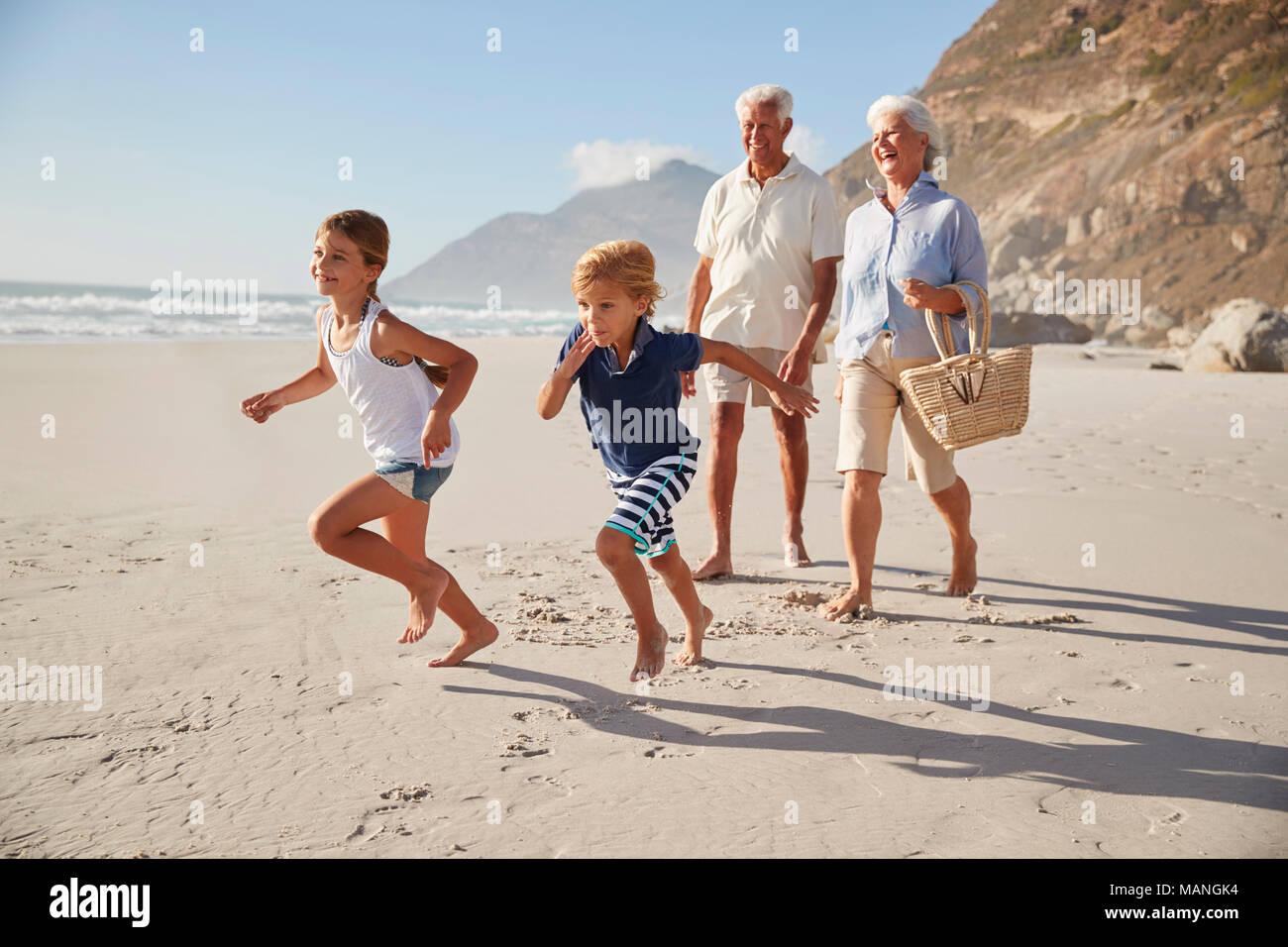 Nonni che corre lungo la spiaggia con i nipoti Immagini Stock
