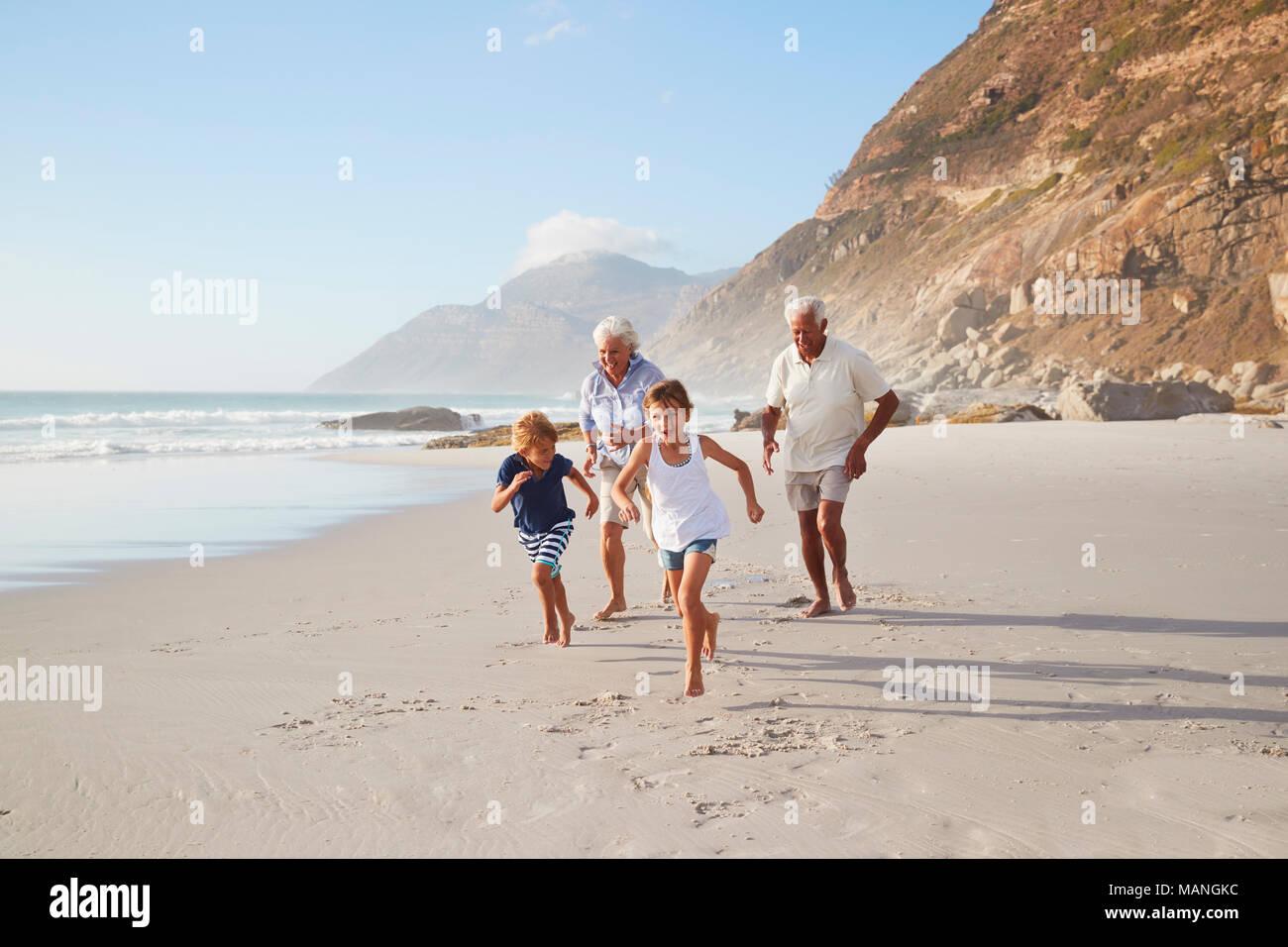 Nonni che corre lungo la spiaggia con i nipoti sulle vacanze estive Immagini Stock