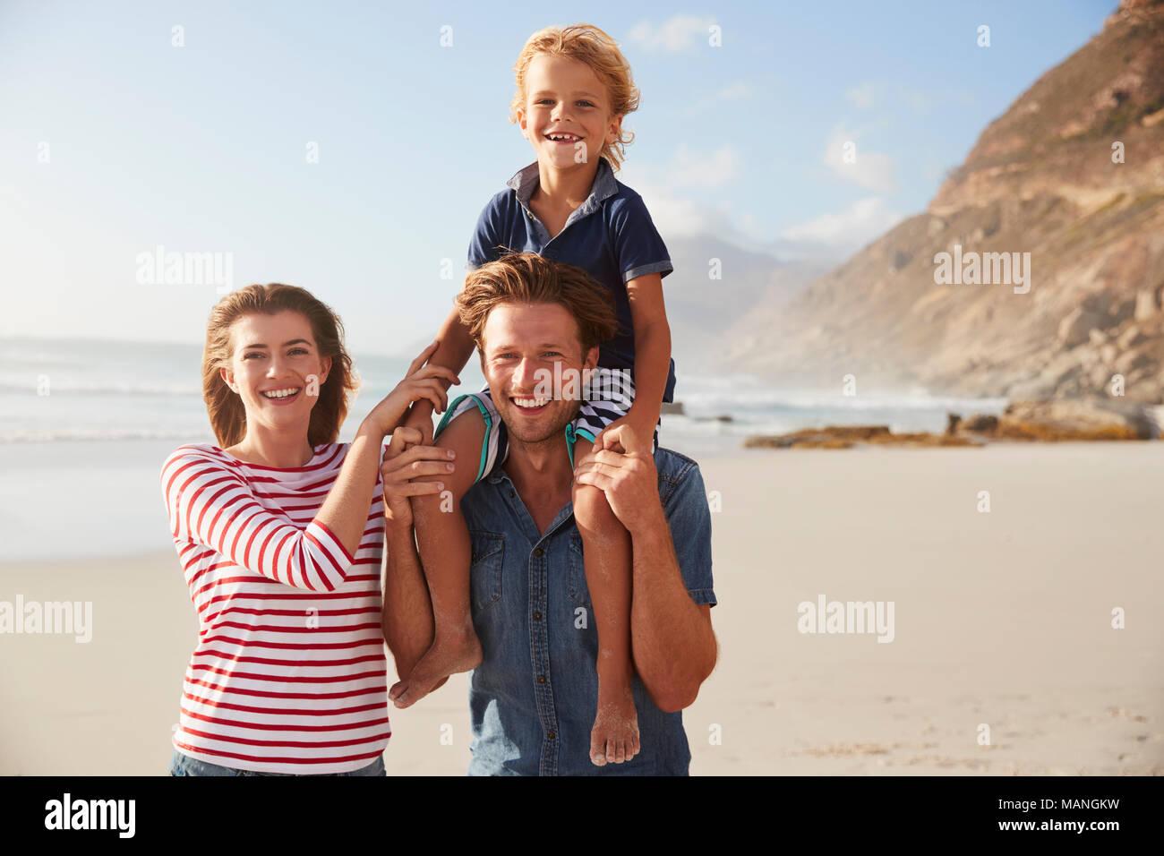 Ritratto di genitori figlio che porta sulle spalle sulla Spiaggia di vacanze Immagini Stock