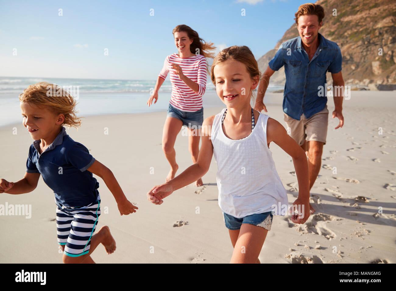 I genitori che corre lungo la spiaggia con i bambini in vacanza estiva Immagini Stock