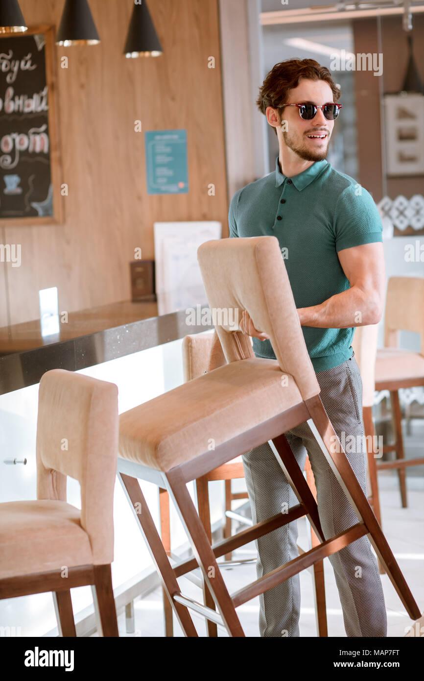 Uomo in bicchieri e maglietta blu e grigio pantaloni azienda sedia. Immagini Stock