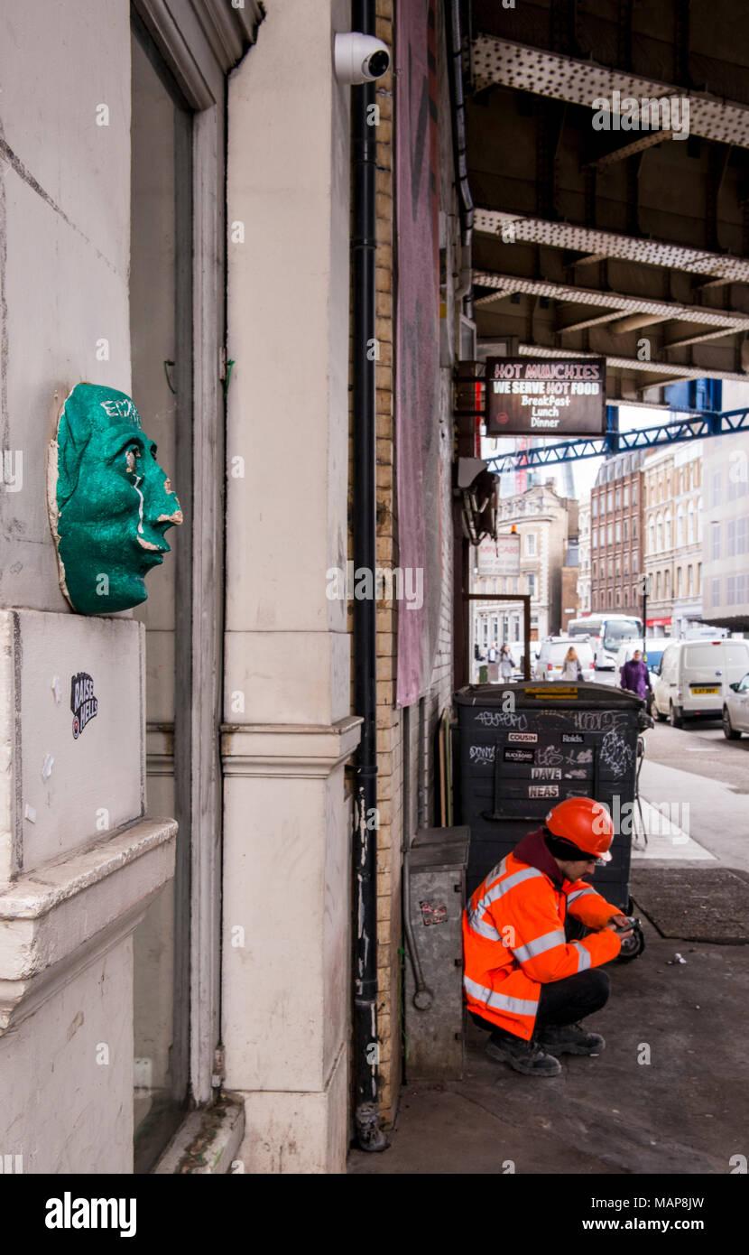Lavoratore in alta visibilità giacca accovacciato dalla parete vicino al Mercato di Borough, Southwark, Londra, Inghilterra, Regno Unito Immagini Stock