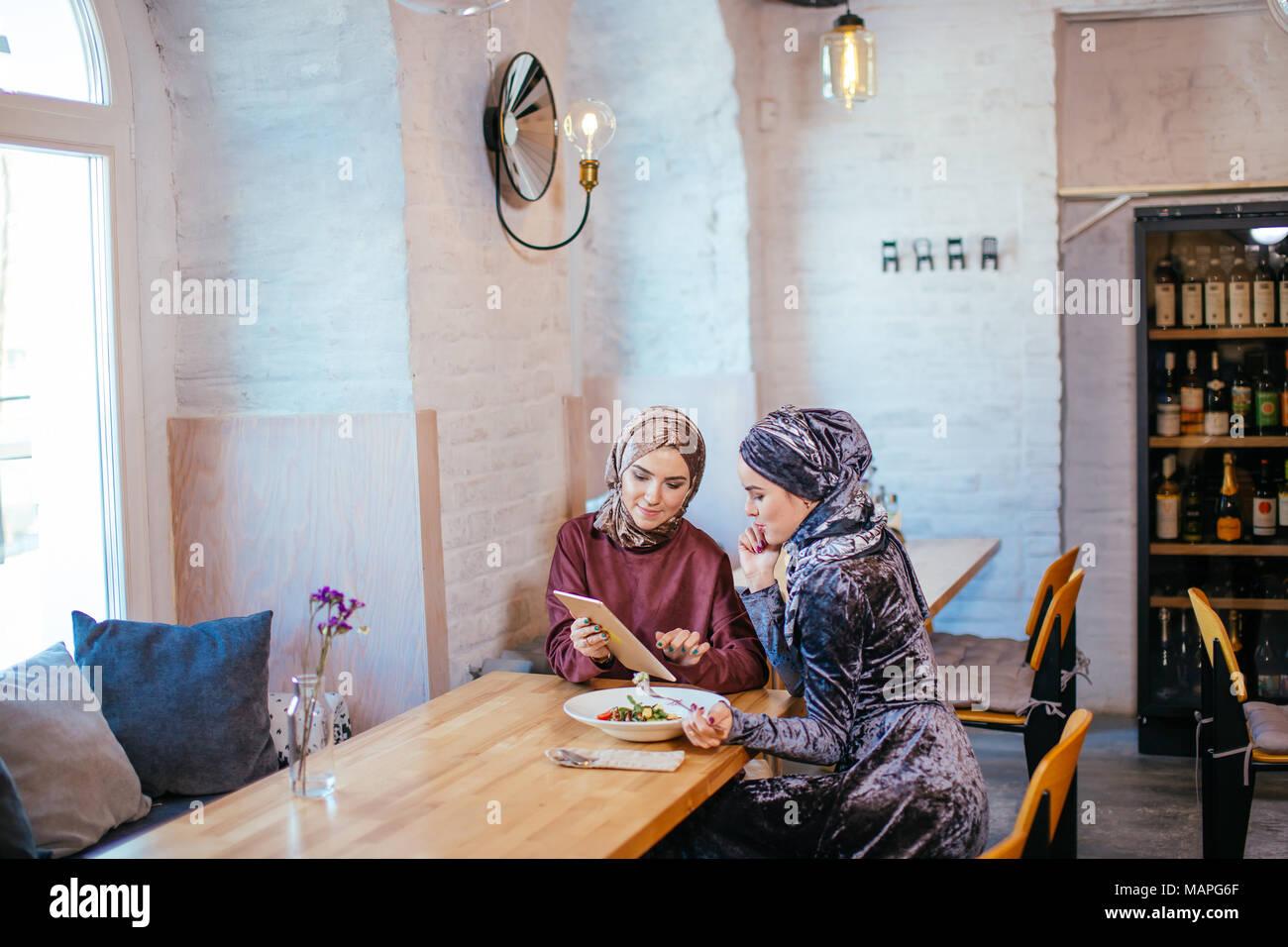Due business partner utilizzando tablet davanti al loro negozio di caffè Foto Stock