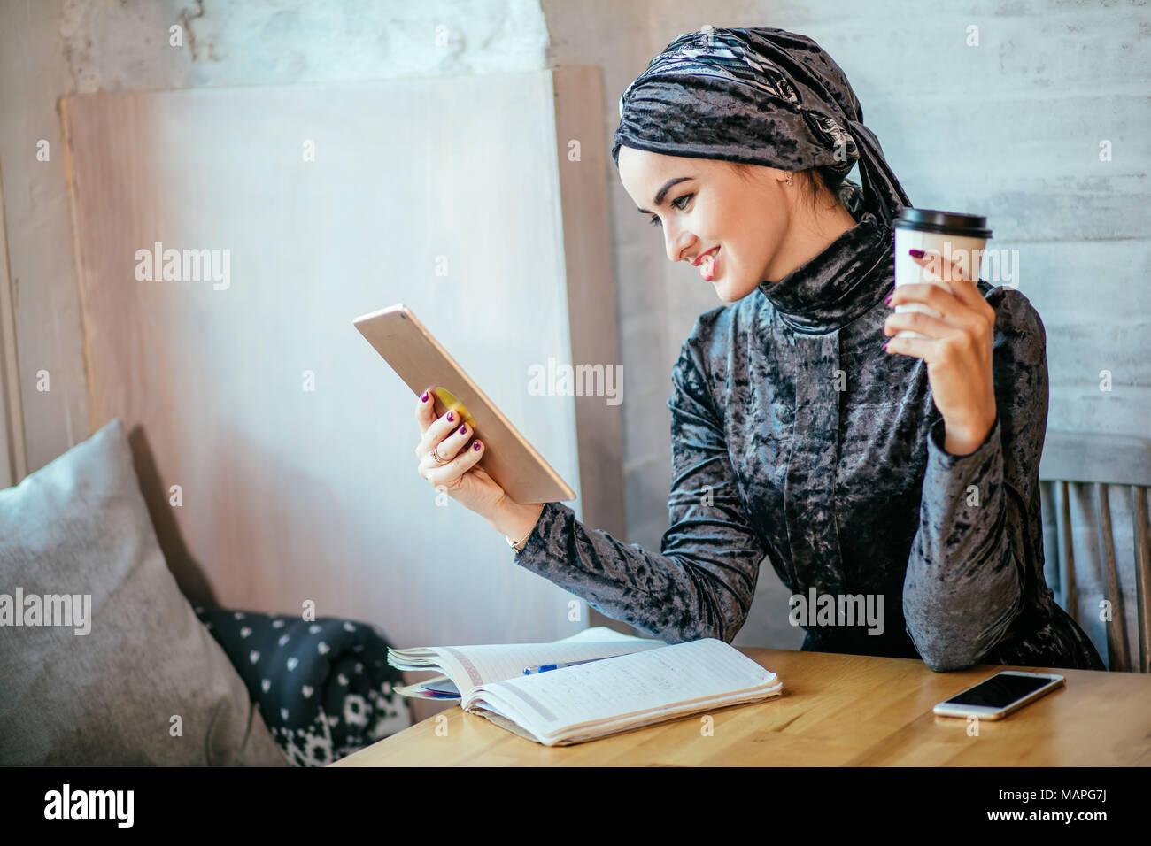 Le donne musulmane lavora con tablet e bere un caffè nella caffetteria Immagini Stock