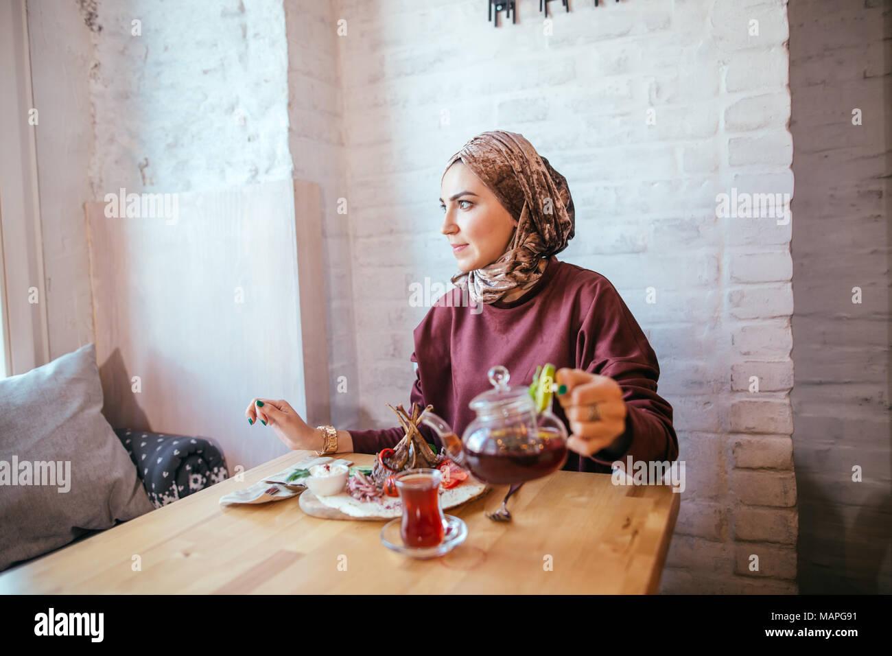 Asian donna musulmana versando del tè sulla tazza Immagini Stock