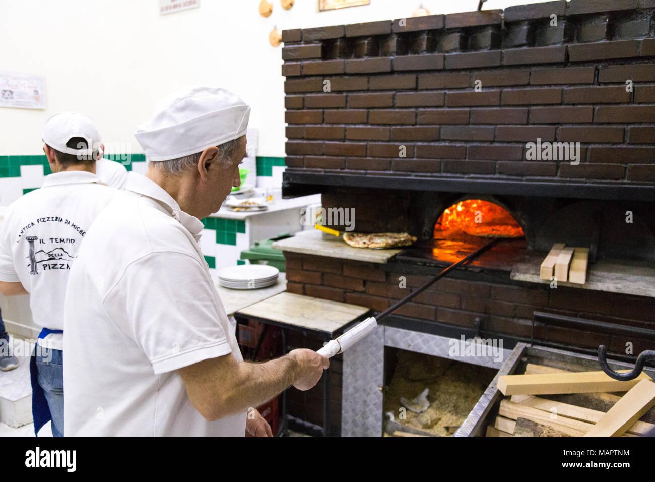 Uomo di cucina italiana tradizionale pizza nel forno a legna presso ...