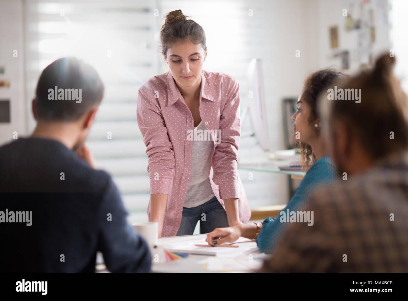 Riunione in ufficio. Una giovane donna presenta il suo progetto Immagini Stock