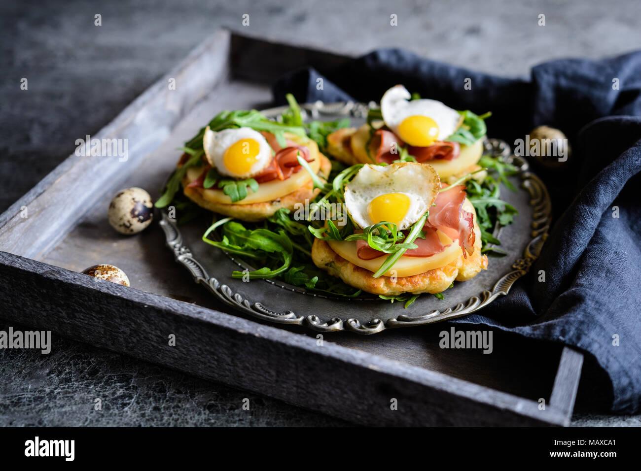 Yogurt salato e scalogno pancake con Black Forrest prosciutto, formaggio affumicato a fette, uovo di quaglia e rucola Immagini Stock
