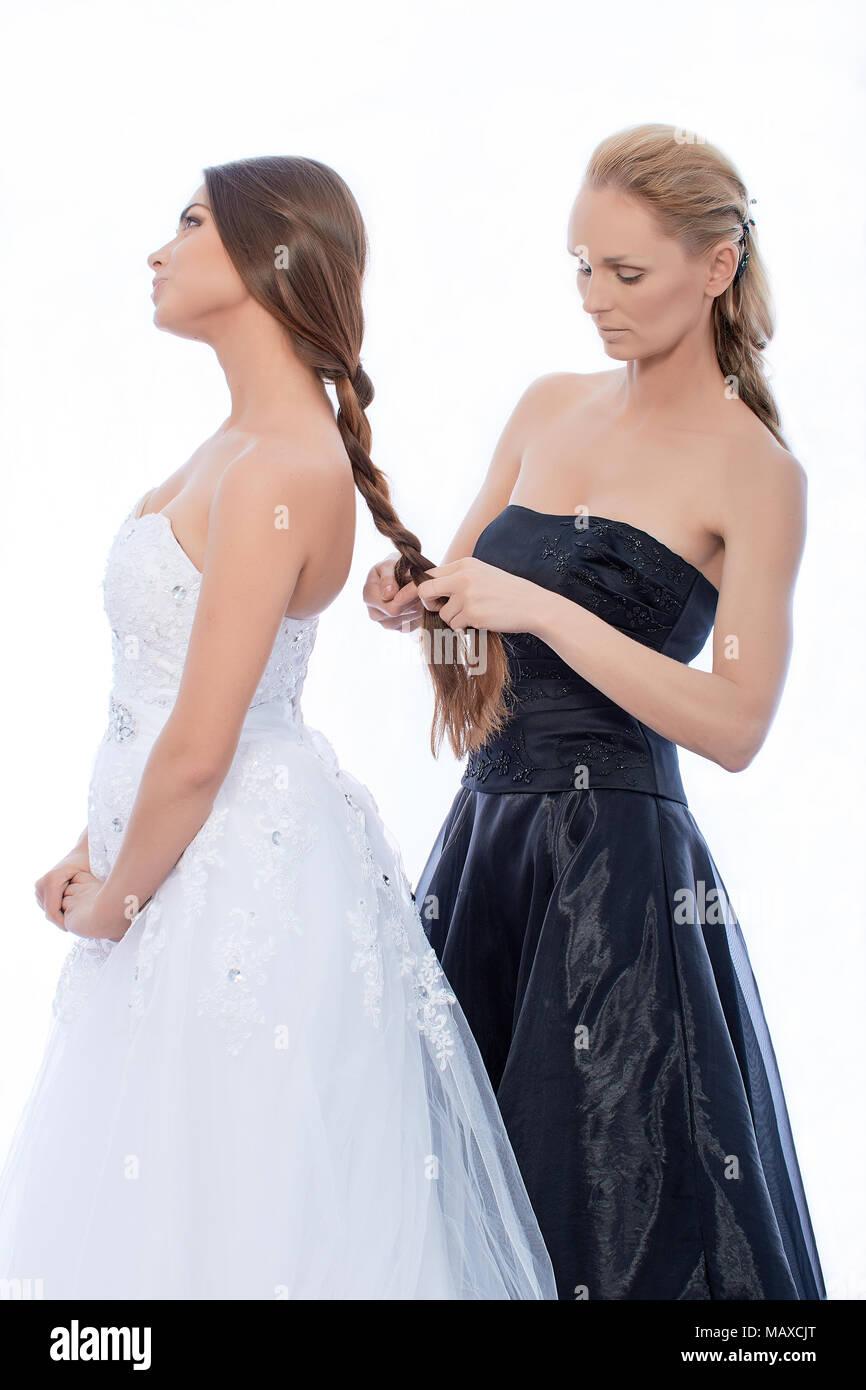 4b9bf3fa38e3 La sposa in un abito bianco e la damigella in un abito nero si stanno  preparando per la cerimonia.