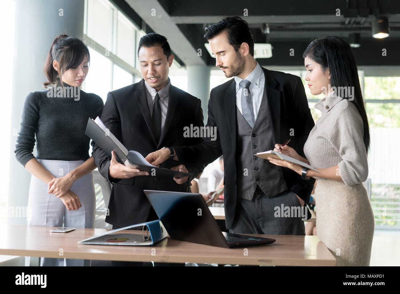 Smart manager spiegando riunione interna al suo team di progetto in un ufficio moderno. La multi etnico persona business group in tuta. Progetto e Business c Immagini Stock