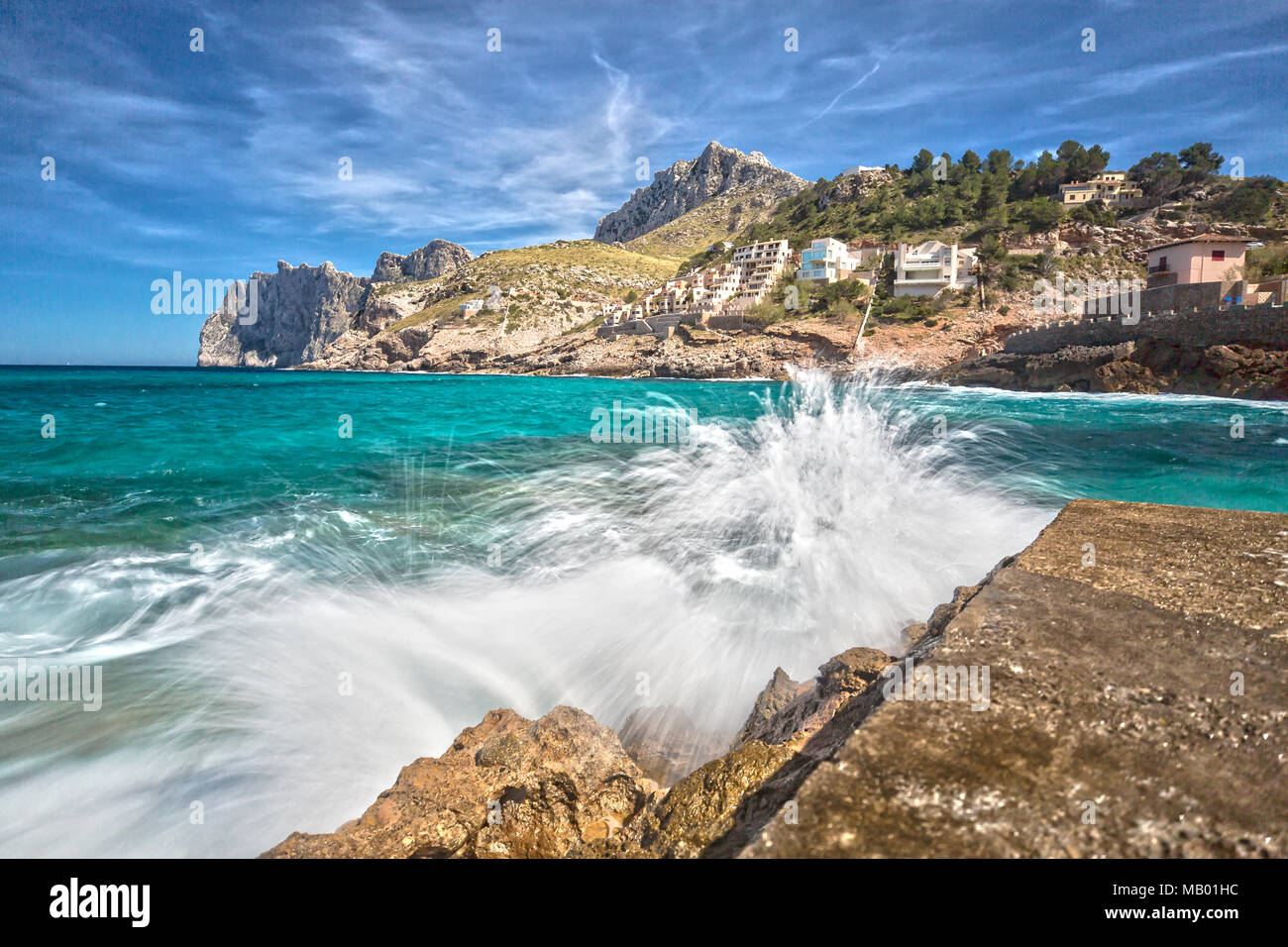 Gli spruzzi di acqua sul molo della piccola cittadina di Cala Sant Vincenc Immagini Stock
