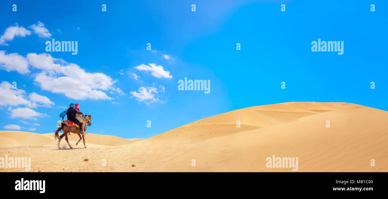 Paesaggio panoramico con equestrians sul cavallo nel deserto del Sahara. Safari Tourism, Tunisia Immagini Stock