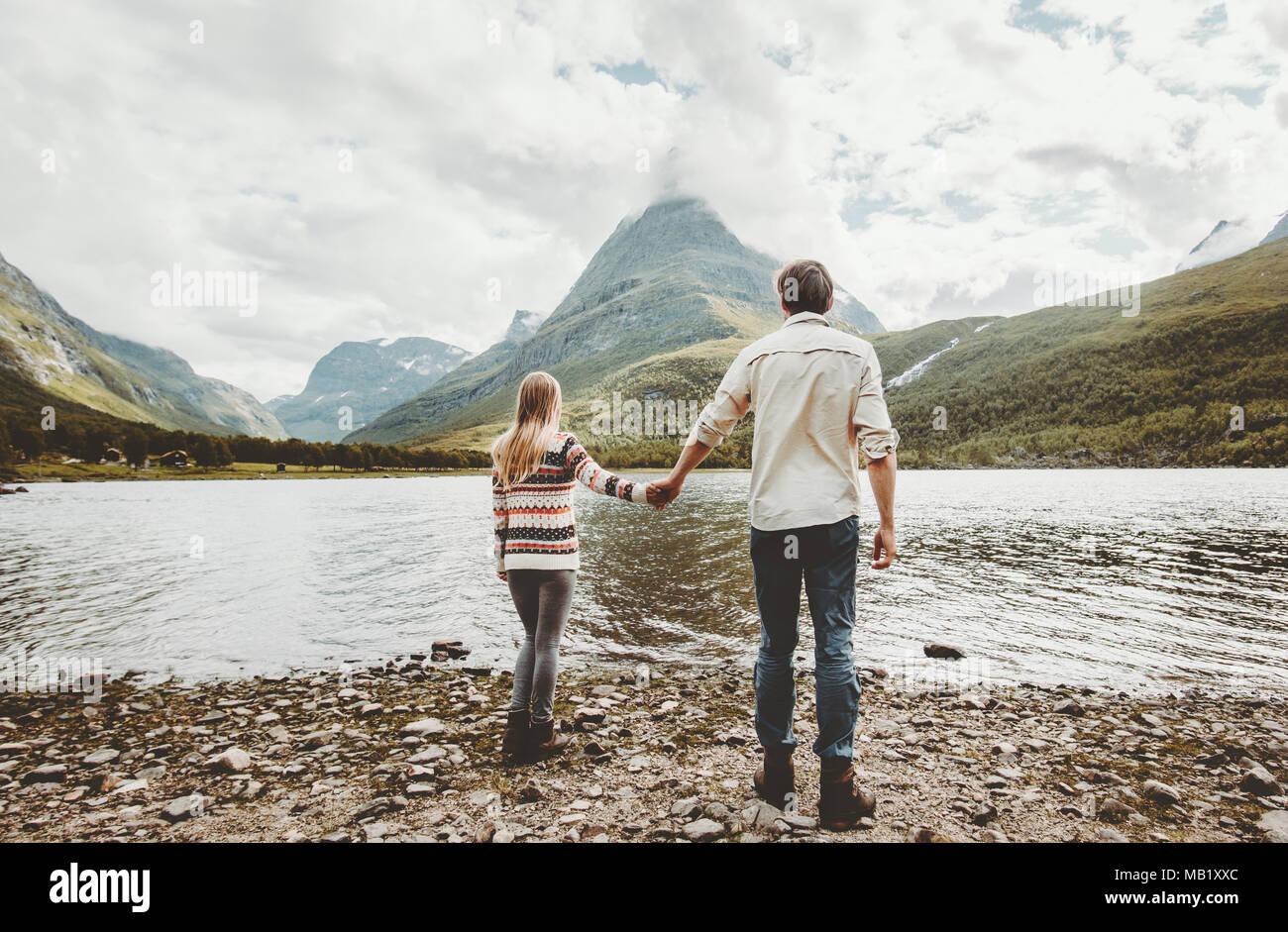 Giovane uomo e donna camminare insieme per mano godendo di montagne e lago di natura outback visualizza famiglia viaggi avventura concetto lifestyle vacat Immagini Stock