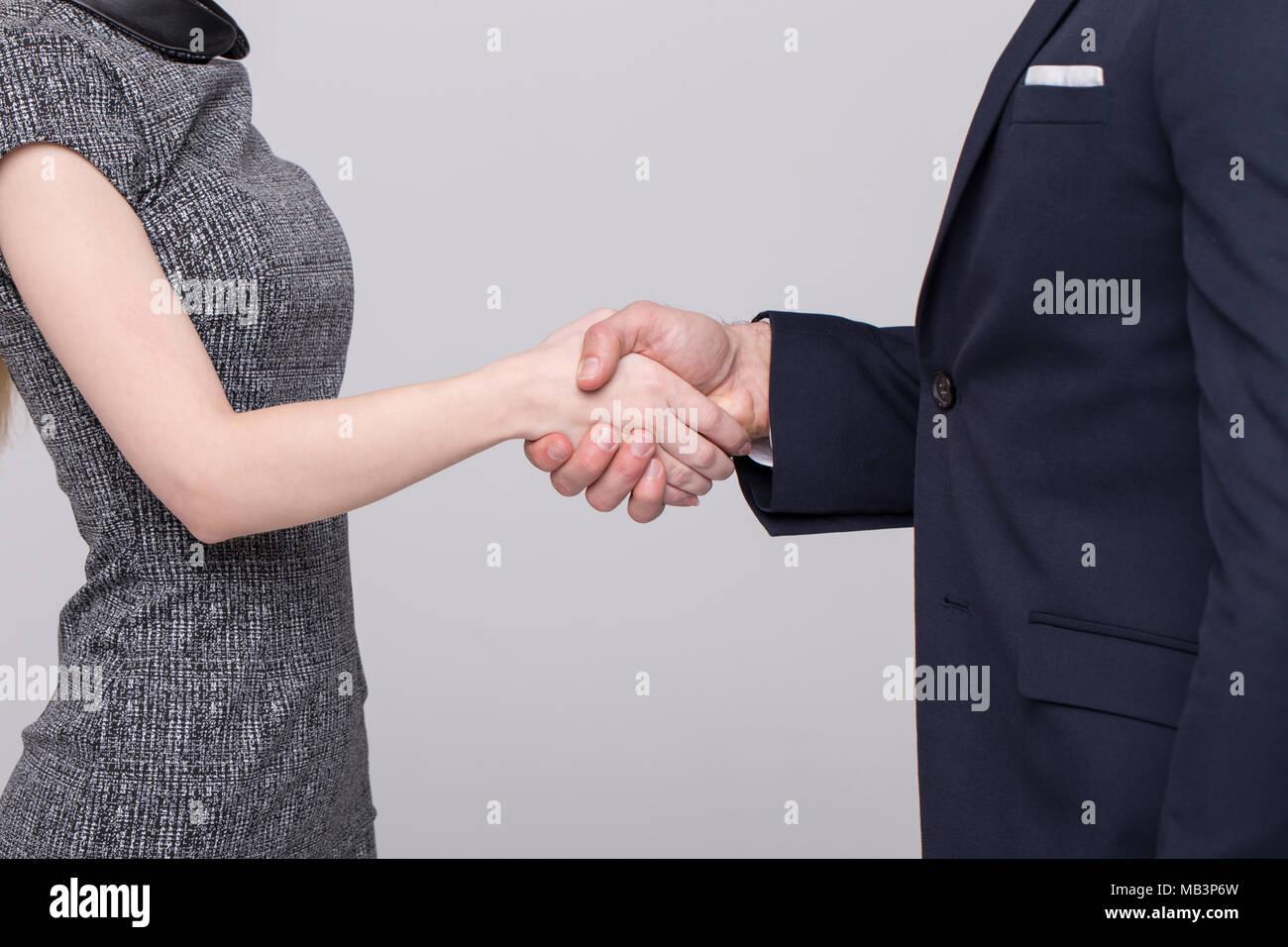 Imprenditore e imprenditrice in abbigliamento formale closeup handshake su sfondo grigio Immagini Stock