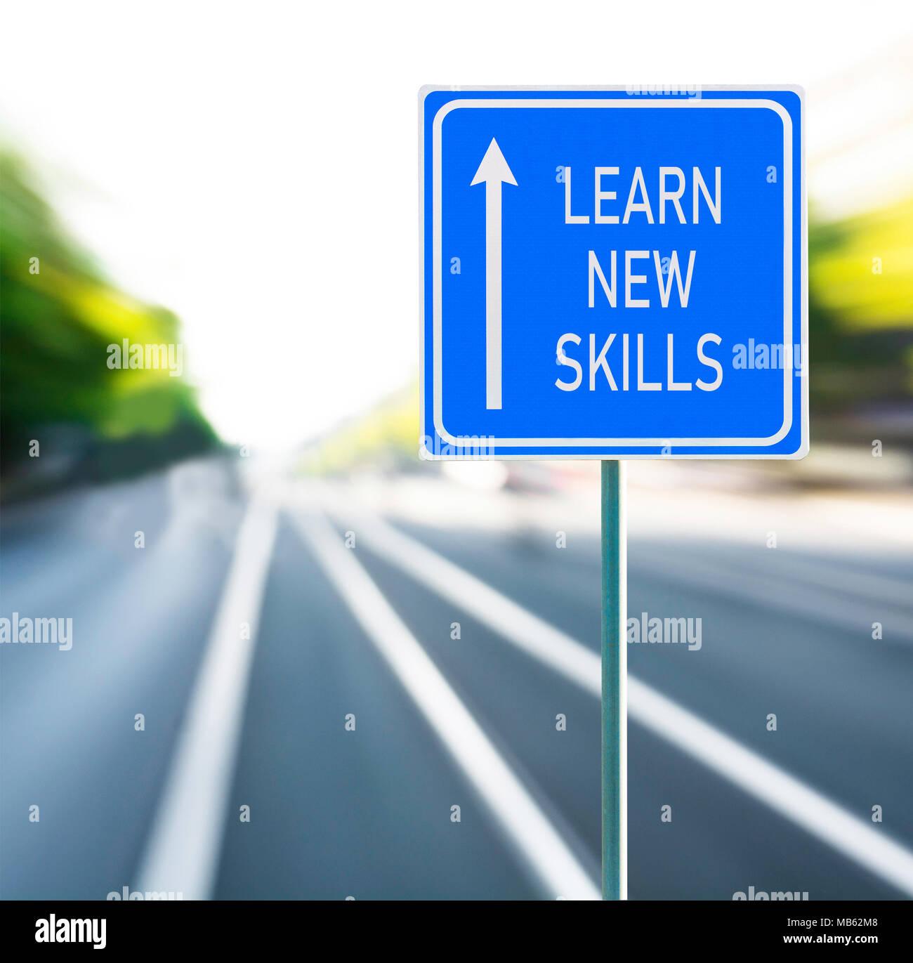 Apprendere nuove abilità motivazionali di frase sul cartello blu con la freccia e sfocata speedy background. Copia dello spazio. Immagini Stock