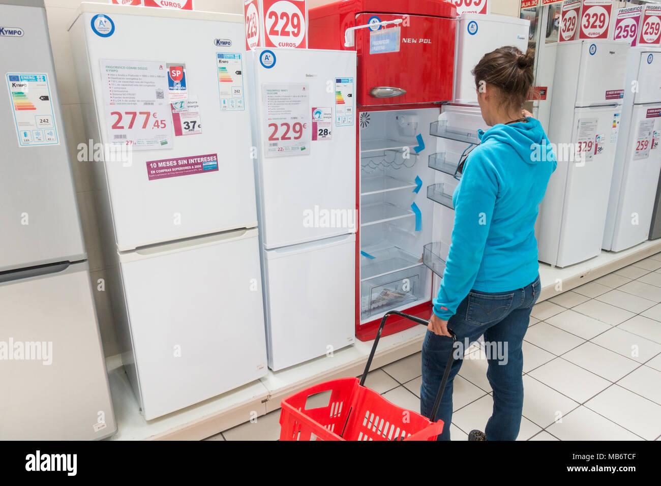 Donna che guarda al nuovo frigorifero/frigoriferi/frigorifero con congelatore in negozio elettrico Immagini Stock