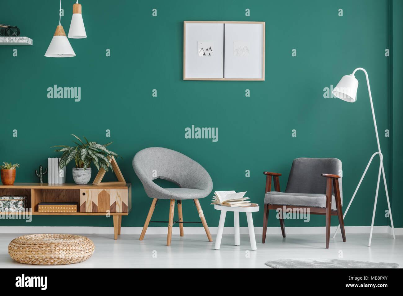 Salotto con parete verde sgabello bianco tra le poltrone di