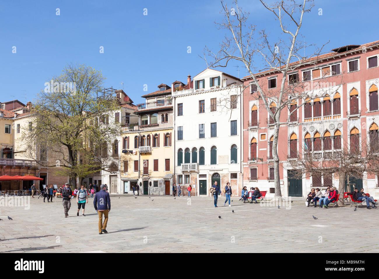 Campo San Polo, San Polo, Venezia, Veneto, Italia in primavera con la gente del posto e i turisti relax su panche e attraversando la piazza di fronte a palazzi Immagini Stock