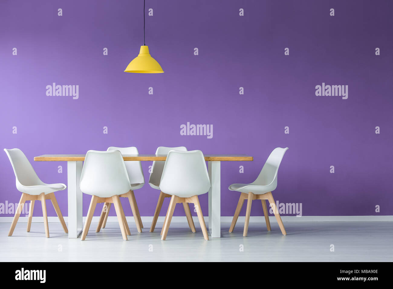Il minimo moderno spazio aperto con interno bianco e sedie di legno intorno a un tavolo da pranzo e lampada gialla contro il muro viola Immagini Stock