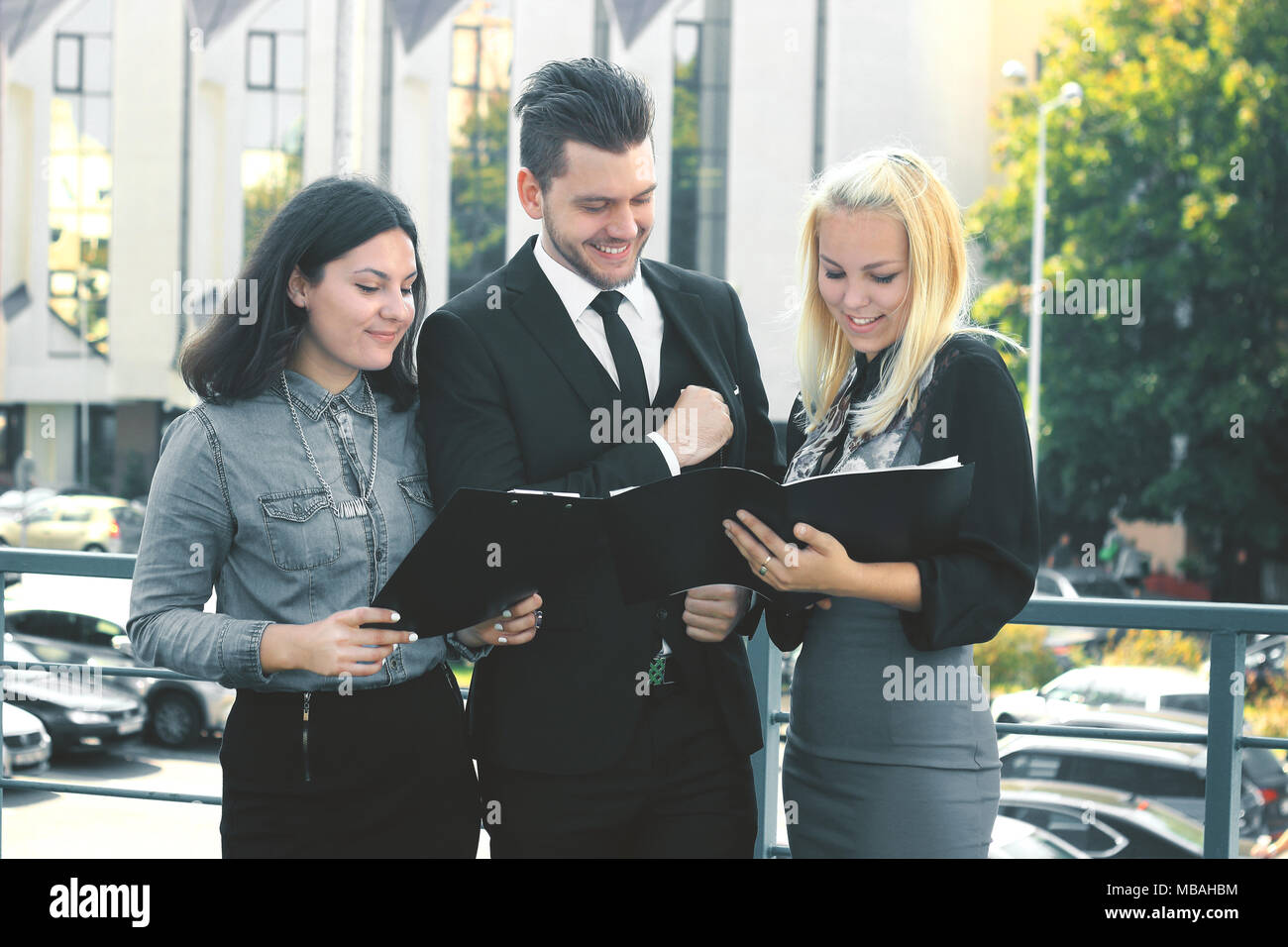 I colleghi la lettura dei documenti in piedi sul balcone dell'ufficio Immagini Stock