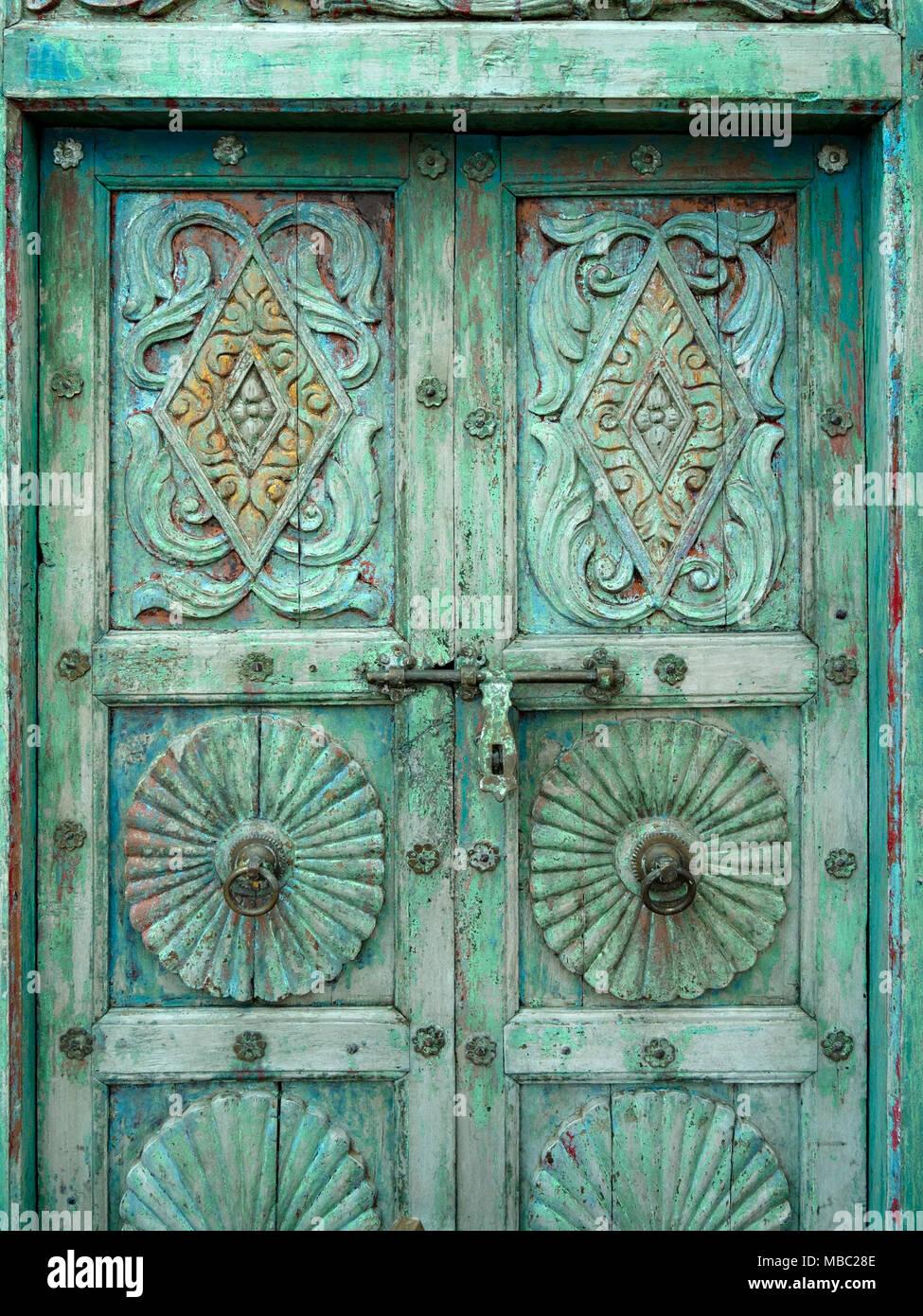 Vecchio addolorato ornati in legno di antiquariato doppie porte in giardino classici del cantiere di bonifica, Ashwell, Rutland, REGNO UNITO Immagini Stock