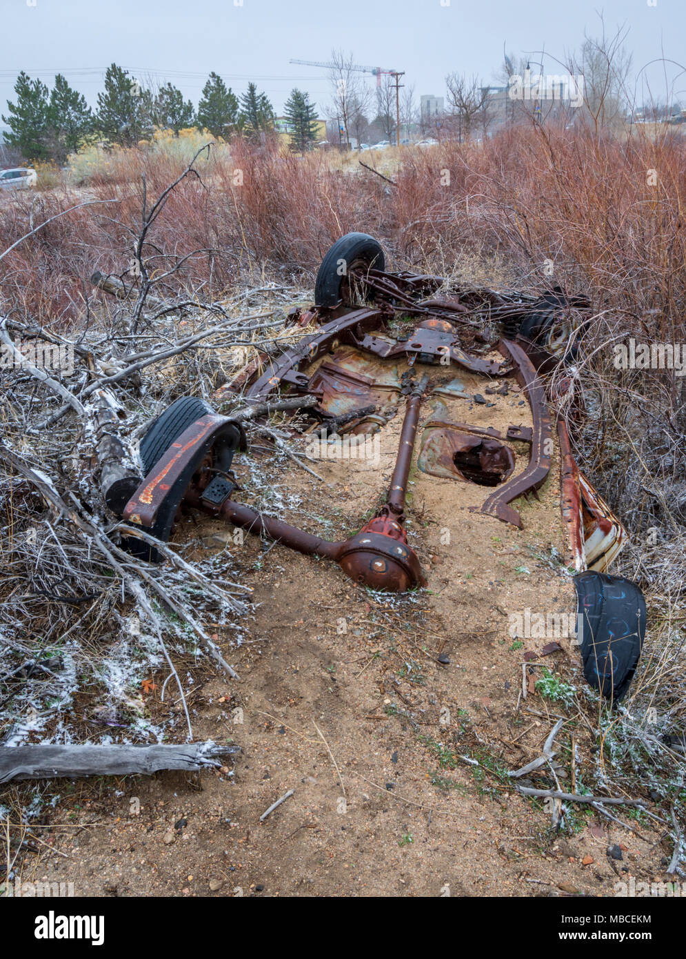 Vecchio arrugginito carro automatica parzialmente sepolti nella sabbia da un vicino torrente. Un contrasto con il nuovo edificio in costruzione la distanza, Colorado. Immagini Stock
